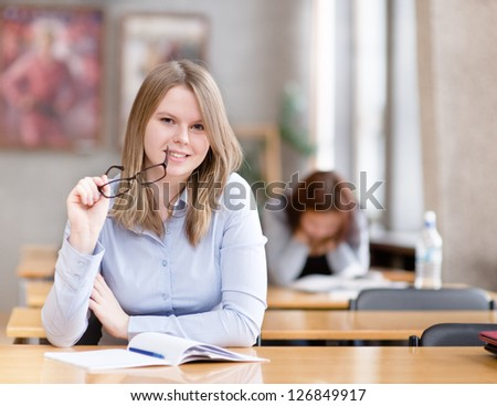 pretty young college student in a library. looking at camera - stock photo