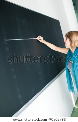 Pretty young college student/teacher writing on the chalkboard/blackboard during a math class (color toned image; shallow DOF) - stock photo