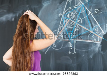 pretty young college student writing on the chalkboard/blackboard during a math class (color toned image; shallow DOF) - stock photo