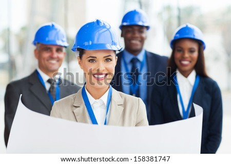 pretty young construction manager holding blue print in front of colleagues - stock photo