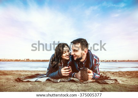 Pretty young couple have fun on the beach - stock photo