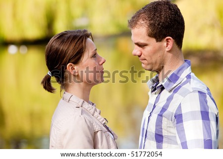 Pretty young couple having a serious talk together - stock photo