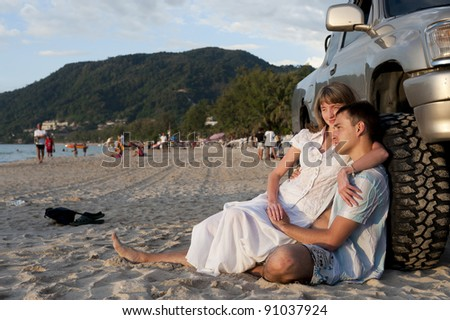 pretty young couple sit near wheel on the sand beach of phuket - stock photo