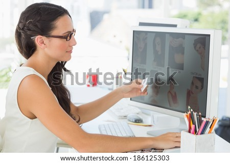 Pretty young editor working at her desk in creative office - stock photo