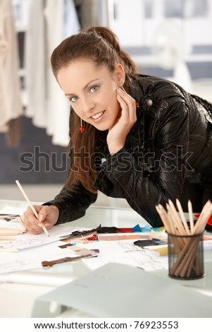 Pretty, young fashion designer working in office, leaning on desk, drawing.? - stock photo