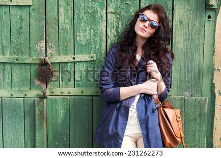 Pretty young fashion smiling brunette woman in sunglasses with leather bag posing outdoor in green wooden door background in spring sunny weather  - stock photo