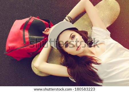 Pretty young fashion woman outdoor summer colorful closeup portrait. Brunette girl posing on the ground with backpack and skate  - stock photo