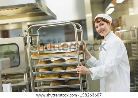 Pretty young female baker pushing a trolley while looking at the camera - stock photo