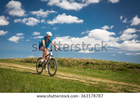 Pretty, young female biker outdoors on her mountain bike (motion blurred image) - stock photo
