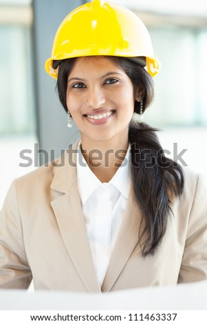 pretty young female construction worker in office - stock photo