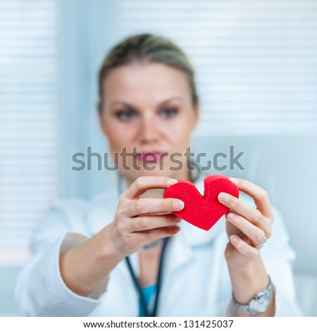 Pretty Young Female Doctor Is Showing a Broken Heart in Ambulance - stock photo