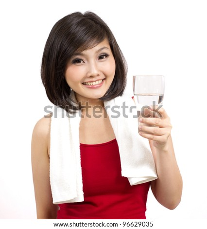 pretty young female holding a glass of water after exercise - stock photo