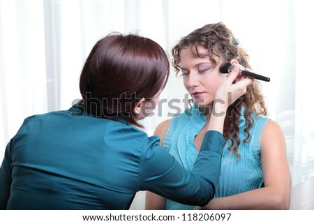 Pretty young female model having her makeup applied before her photoshoot. - stock photo