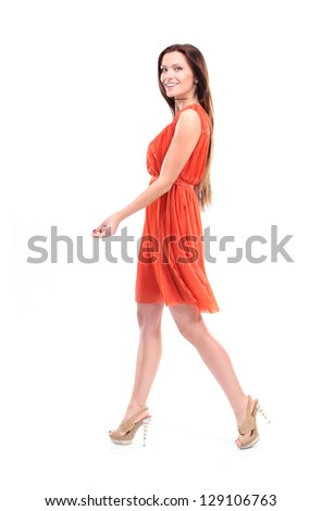 Pretty young female model in dress walking on white background and smiling - Copysapce - stock photo