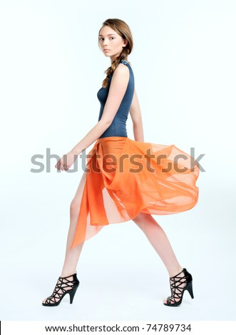 Pretty young female model in orange dress walking on white background - stock photo