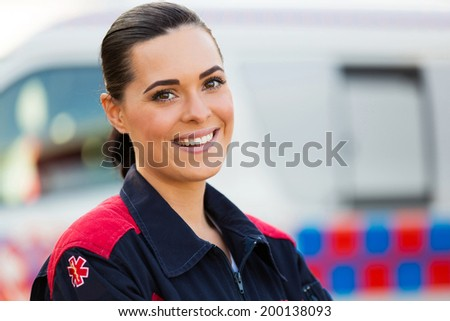 pretty young female paramedic looking at the camera - stock photo
