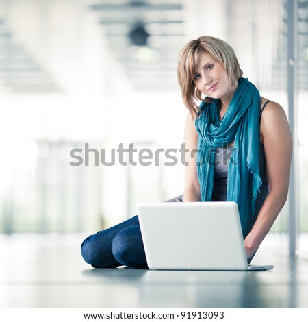 Pretty young female student/businesswoman with a laptop computer at college/university campus/work (shallow DOF; color toned image) - stock photo