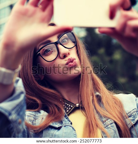 Pretty young female tourist makes selfie. Beautiful urban woman taking picture of herself. Filtered image.  - stock photo