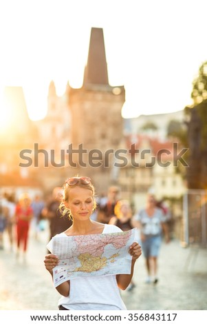 Pretty young female tourist studying a map at the Trajan's forum in Rome, Italy (dome of the Santissimo Nome di Maria church in the background) - stock photo