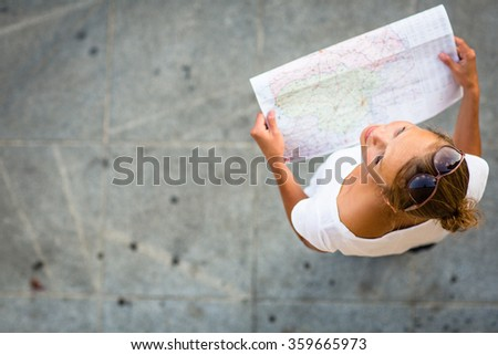 Pretty young female tourist studying a map, enjoying discovering a new city, looking excited (shallow DOF; color toned image) - stock photo