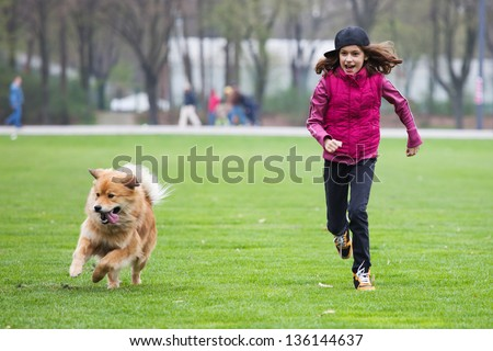 pretty young girl and her cute Elo dog run over the green meadow - stock photo