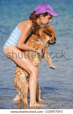 pretty young girl carries an Elo puppy in the sea water - stock photo