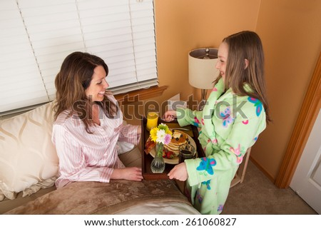 Pretty young girl delivering breakfast in bed to her Mom for Mother's Day - stock photo