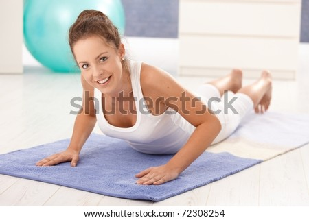 Pretty young girl doing exercises on floor at home, smiling.? - stock photo