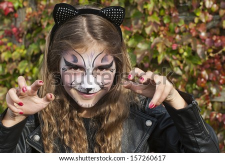 Pretty, young girl dressed as a black cat for Halloween - stock photo
