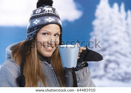 Pretty young girl dressed up warm for skiing wearing cap and gloves drinking hot tea smiling front of winter landscape .? - stock photo