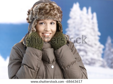 Pretty young girl dressed up warm in coat, fur-hat and gloves, smiling front of winter landscape.? - stock photo