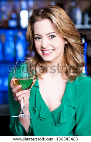 Pretty young girl enjoying sparkling wine. - stock photo