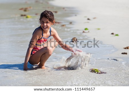 pretty young girl having fun by playing at the beach - stock photo