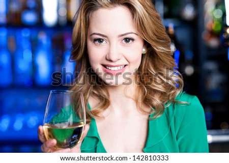 Pretty young girl having wine at a bar - stock photo