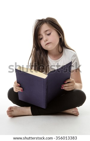 pretty young girl is sitting cross legged whilst reading her book isolated on white  - stock photo