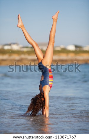 pretty young girl makes a handstand in the sea - stock photo