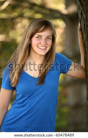 pretty young girl outside by tree smiling - stock photo