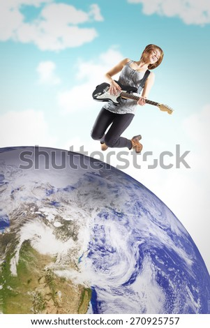 Pretty young girl playing her guitar against blue sky - stock photo