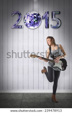 Pretty young girl playing her guitar against grey room - stock photo