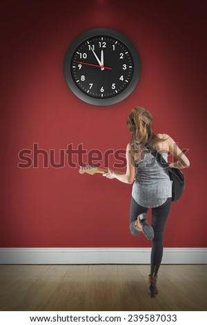 Pretty young girl playing her guitar against room with wooden floor - stock photo