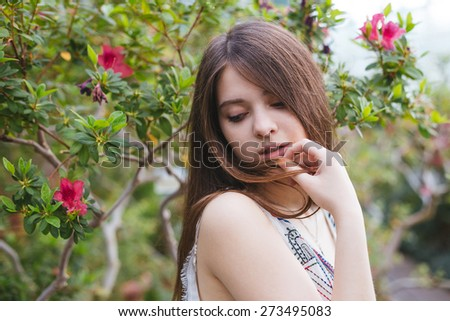 Pretty young girl posing with red flowers in greenhouse - stock photo