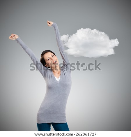 Pretty young girl puts her hands up, grey background - stock photo