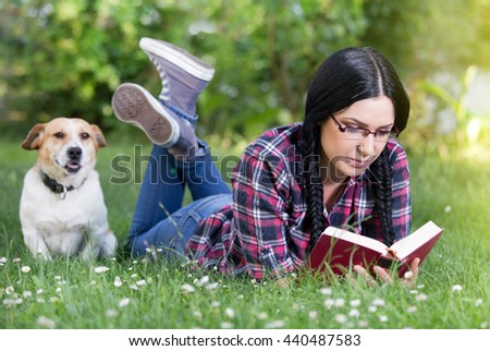 Pretty young girl reading book on grass in park with dog beside her - stock photo