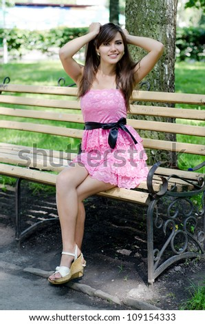 Pretty young girl sitting on a park bench - stock photo