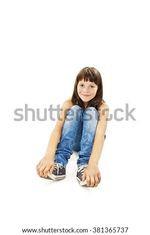 Pretty young girl sitting on the floor in jeans. Isolated on white background  - stock photo