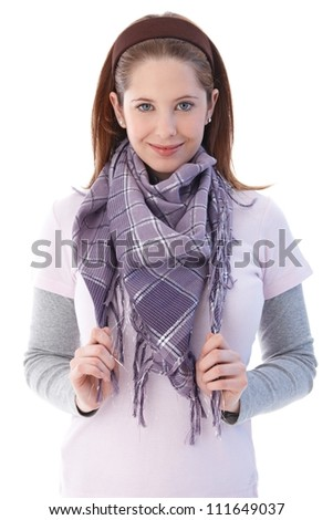 Pretty young girl smiling at camera, wearing scarf. - stock photo