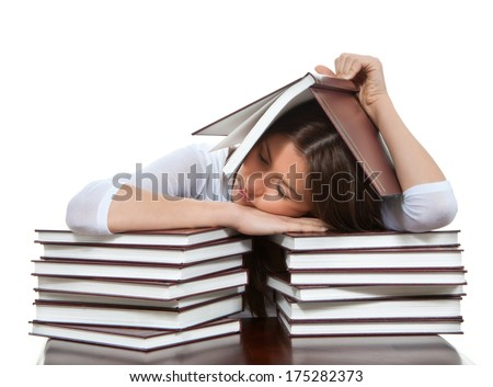 Pretty young girl student lying on the table tired sleeping under stacks of books, over textbooks on a white background - stock photo
