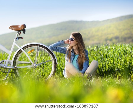 Pretty young girl with bike in green field - stock photo