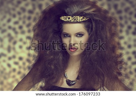 pretty young girl with creative curly hair-style posing with sexy make-up and leopard accessory in the hair and necklace  - stock photo
