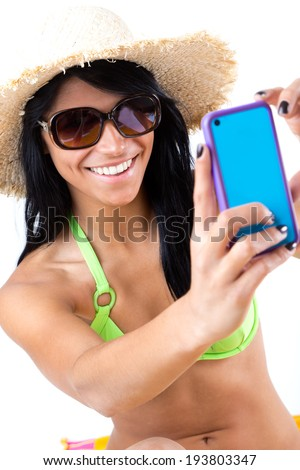 Pretty young girl with green bikini taking selfies with her smart phone . Isolated on white - stock photo